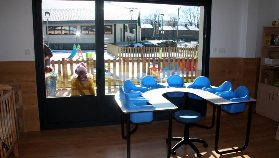 Una aula d'una llar d'infants i on es veuen alumnes del centre al pati.