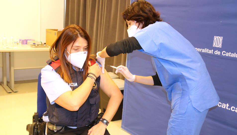 Una agent dels Mossos d'Esquadra rebent uan dosi de la vacuna d'AstraZeneca.