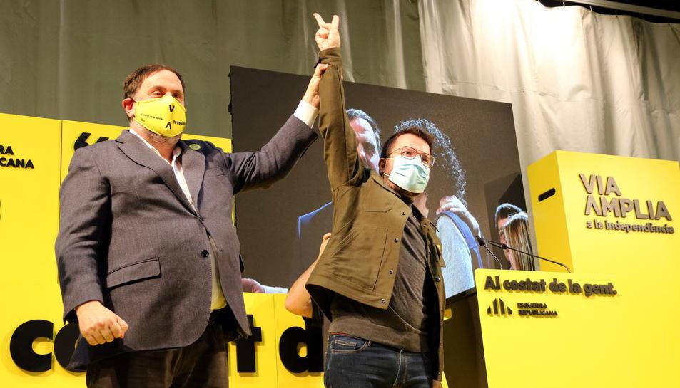 Oriol Junqueras i Pere Aragonès saludant al públic durant un acte de campanya.