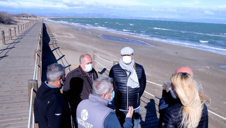 Pla general d'un grup de veïns de Riumar a la zona nord de la platja, on el mar s'aproxima a les passarel·les de fusta.