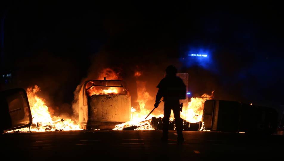 Silueta d'un agent dels antiavalots dels Mossos d'Esquadra davant de diversos contenidors cremats durant les protestes.