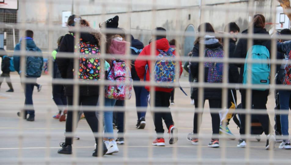 Diversos nens i nenes entrant a l'escola.