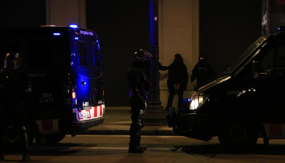 Un home detingut, de cara a la paret, entre diversos agents dels Mossos i furgonetes, a Plaça Catalunya.