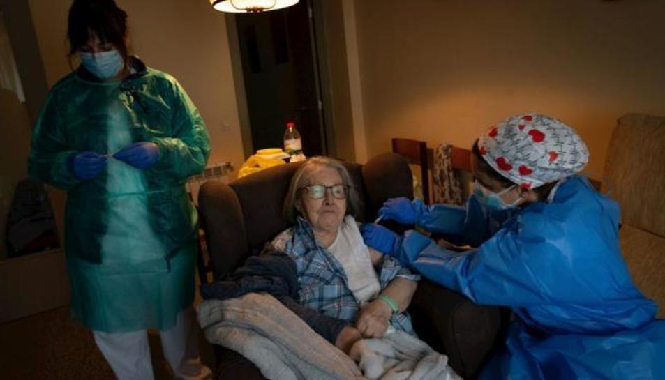 Una infermera administra la primera dosi de la vacuna BioNTech Pfizer a una pacient.