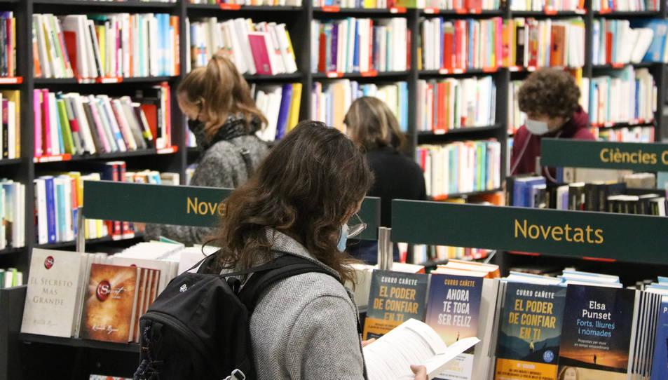 Pla conjunt de diverses persones mirant llibres en una llibreria.