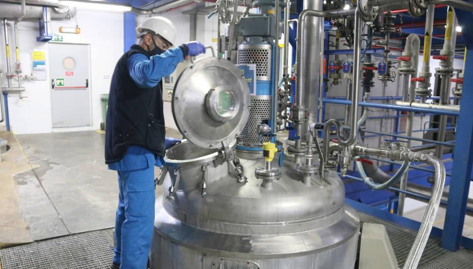 Un treballador manipulant una màquina.