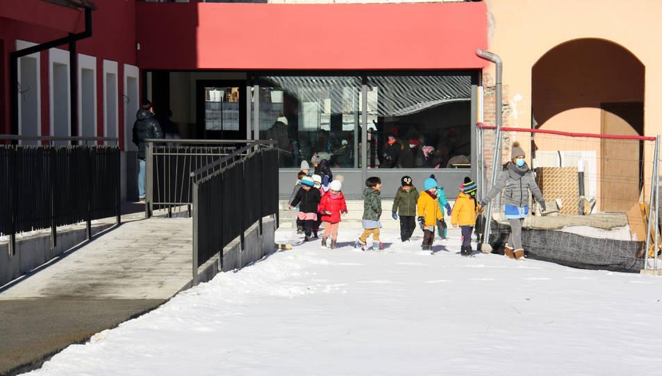 Alumnes d'una escola sortint al pati des del nou edifici.
