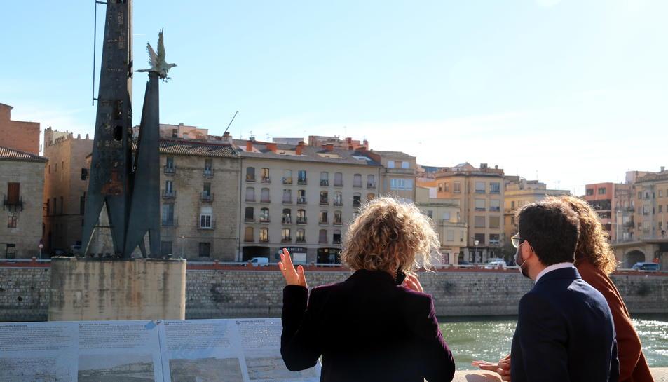 Pla obert del vicepresident Pere Aragonès, la consellera de Justícia Ester Capella i l'alcaldessa de Tortosa Meritxell Roigé, d'esquenes, mirant el monument franquista.
