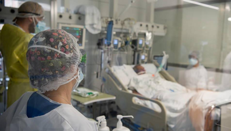 Diversos sanitaris del Clínic a l'habitació d'un malalt crític de covid.