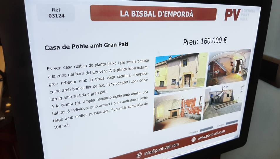 Un cartell d'una casa en venda en una immobiliària de la Bisbal d'Empordà.