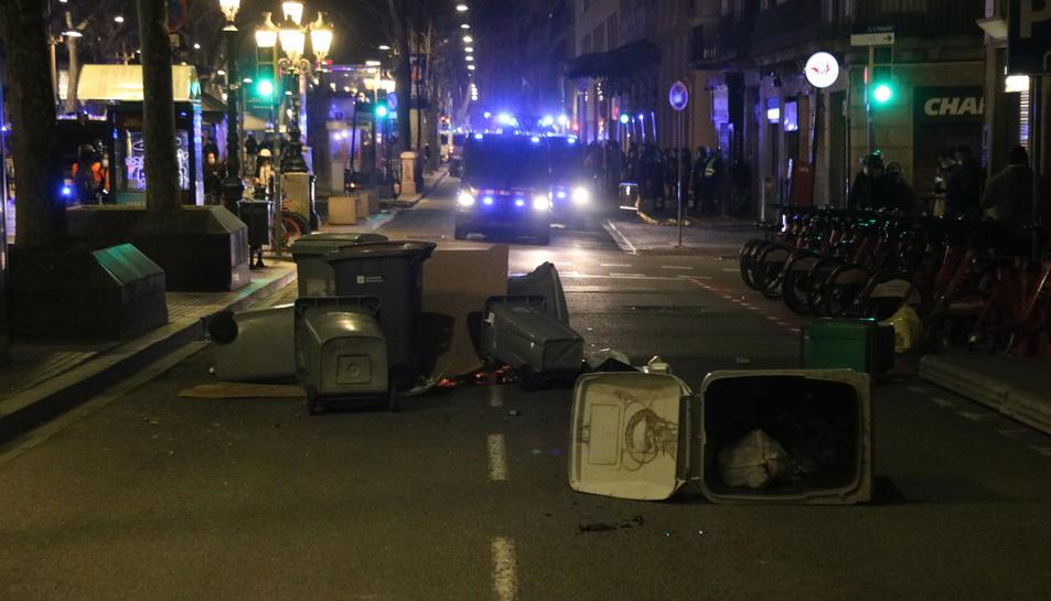 Una petita barricada amb contenidors a la Rambla de Barcelona, amb unes furgonetes dels Mossos en segon pla.