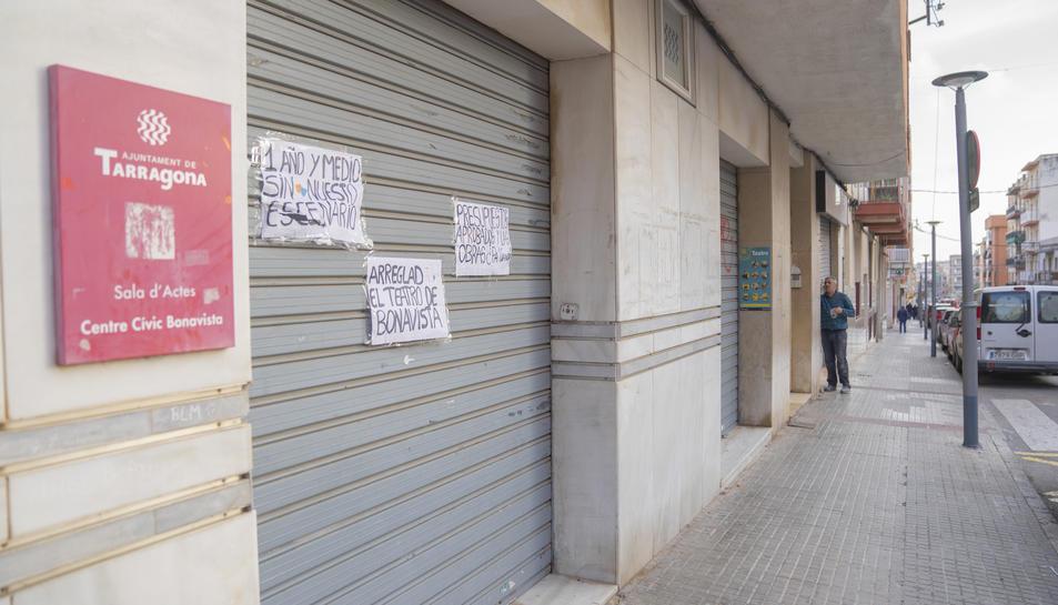 Imatge de la porta d'entrada al teatre amb els cartells dels joves del barri reclamant l'obertura.