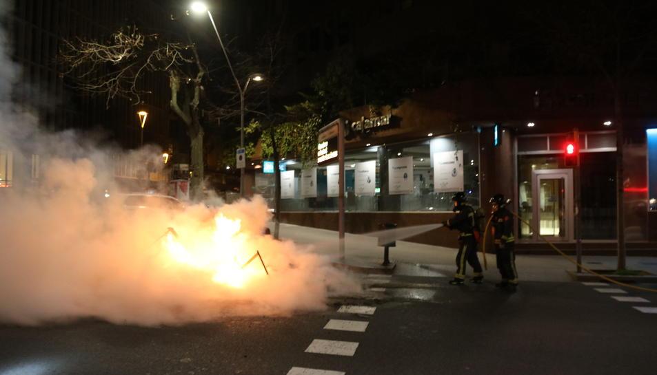Els Bombers apagant una de les barricades que s'han fet a Barcelona durant els aldarulls.