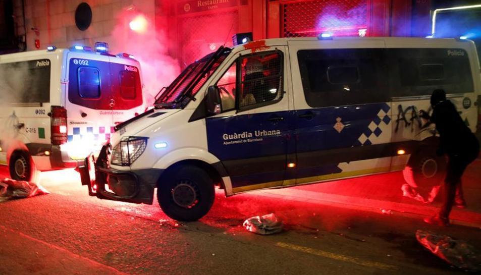 os manifestantes atacan la comisaría de La Rambla con cócteles molotov durante la marcha para pedir la libertad de Pablo Hasel, hoy sábado en Barcelona.