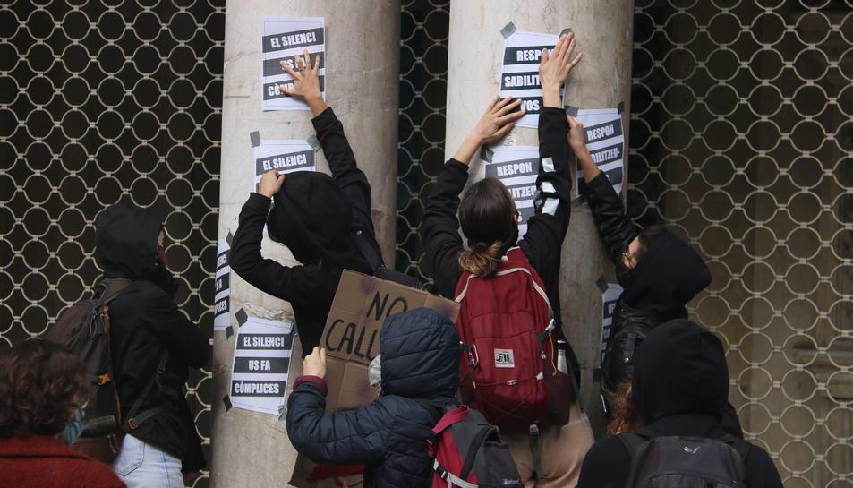 Estudiants d'arts en viu encartellen la façana del Teatre Coliseum durant la manifestació per la vaga convocada contra els casos d'abusos de poder i assetjament denunciats a l'IT.