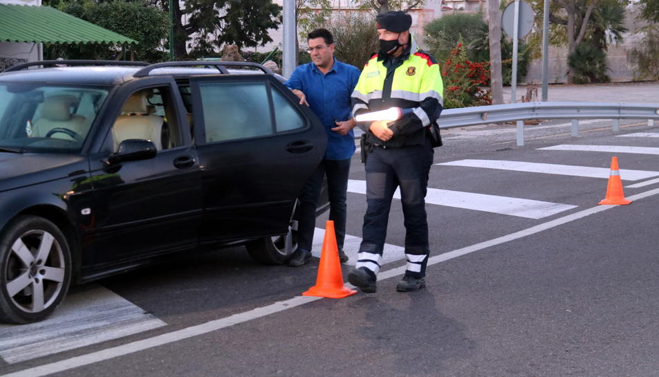 Pla general d'un conductor mostrant la documentació i els certificats de mobilitat a un agents dels Mossos en el control a la intersecció de l'N-340 a les Cases d'Alcanar.