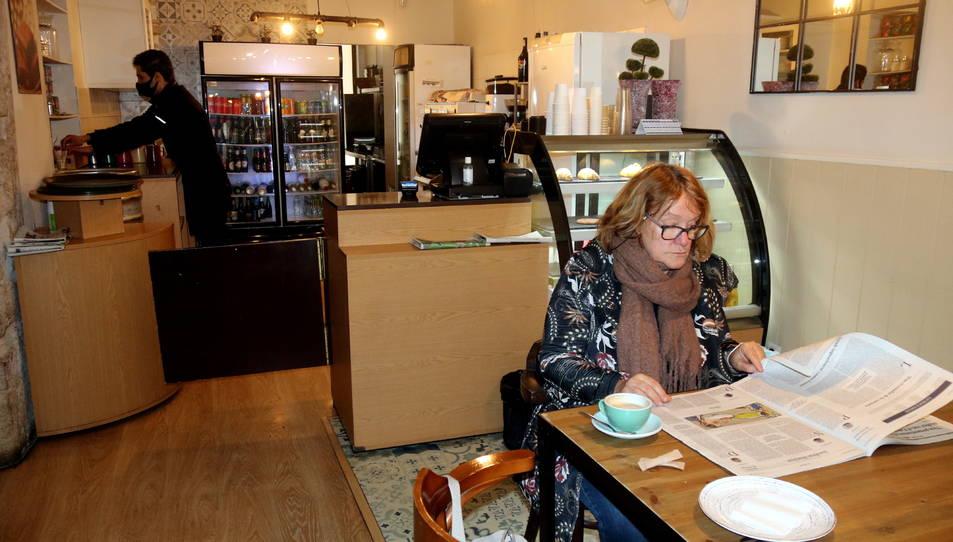 Una clienta esmorzant en un bar.