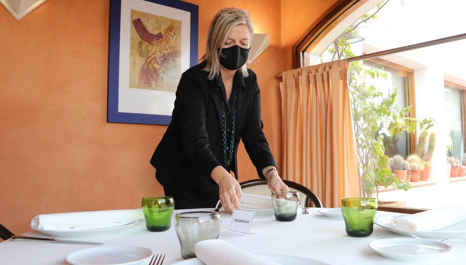Una restauradora preparant una taula per menjar.