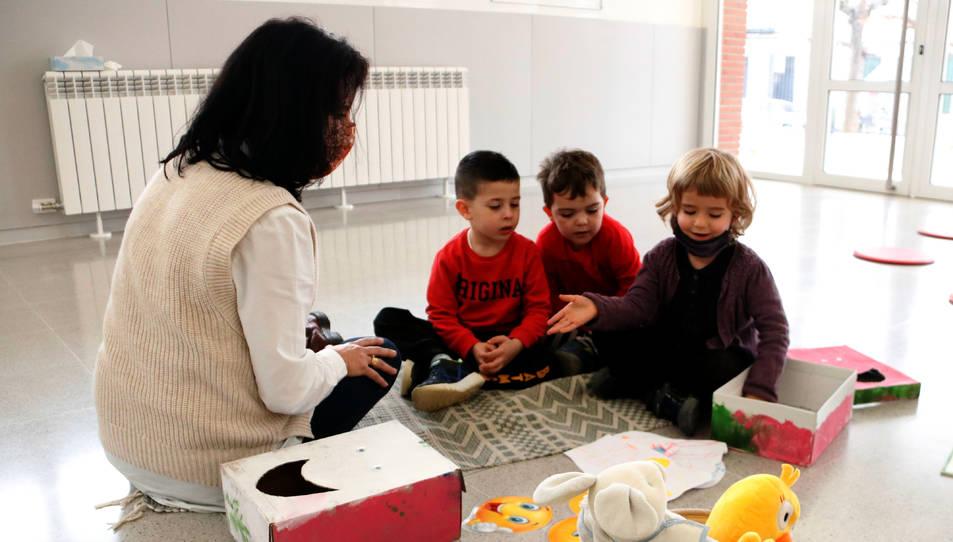 Tres alumnes de P-3 escoltant les explicacions de la mestra.