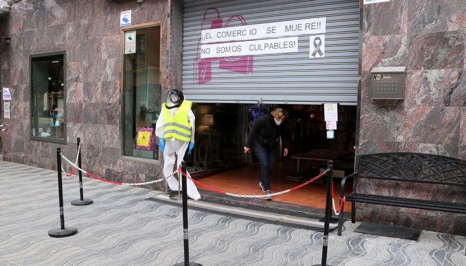 Una comerciant sortint d'una botiga de Cambrils que està aixecant la persiana per protestar contra el tancament dels establiments els caps de setmana.