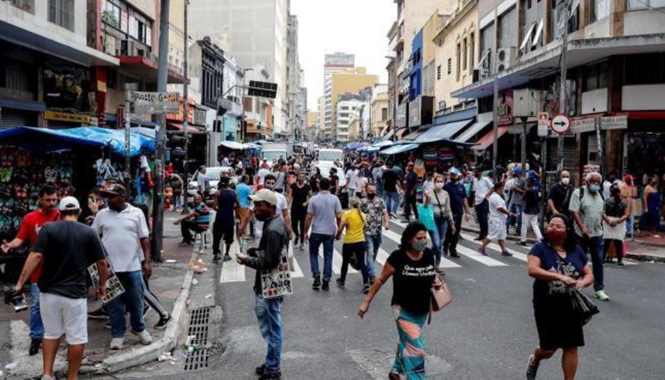 Desenes de persones caminen per una via comercial del centre de Sao Paulo.