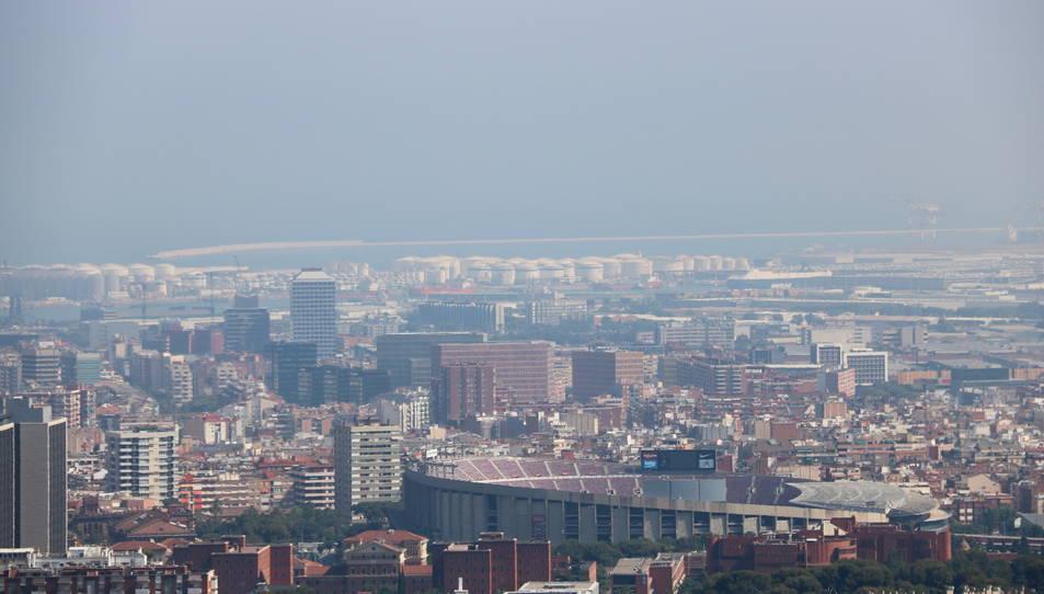 Barcelona amb el Camp Nou en primer pla i el port de fons amb boira per pol·lució al fons.