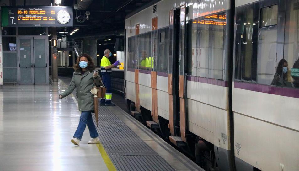 Pla obert d'una usuària de Rodalies sortint d'un tren a l'andana de l'estació de Sants de Barcelona.
