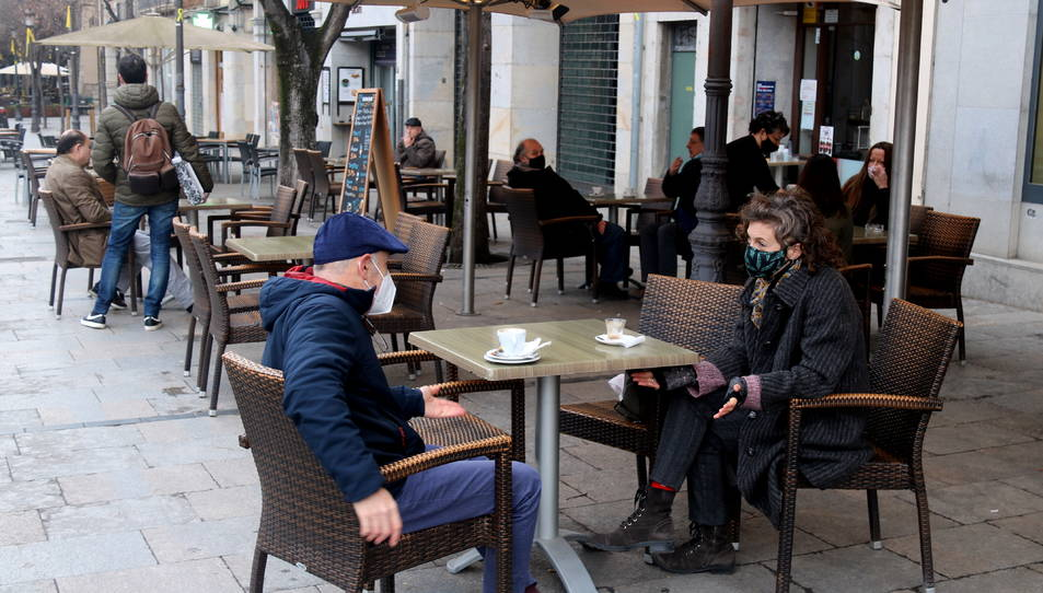 Clients esmorzant en una terrassa de la Rambla de Girona.