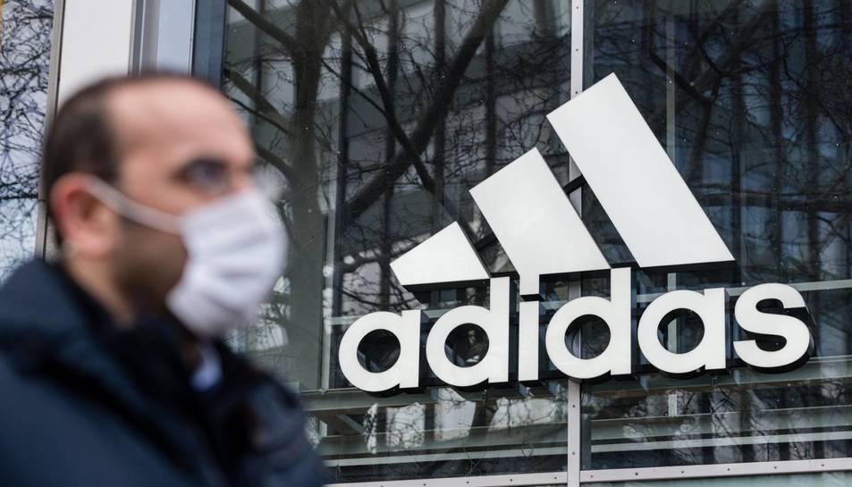 Logotip d'Adidas reflectit en una de les seves botigues.