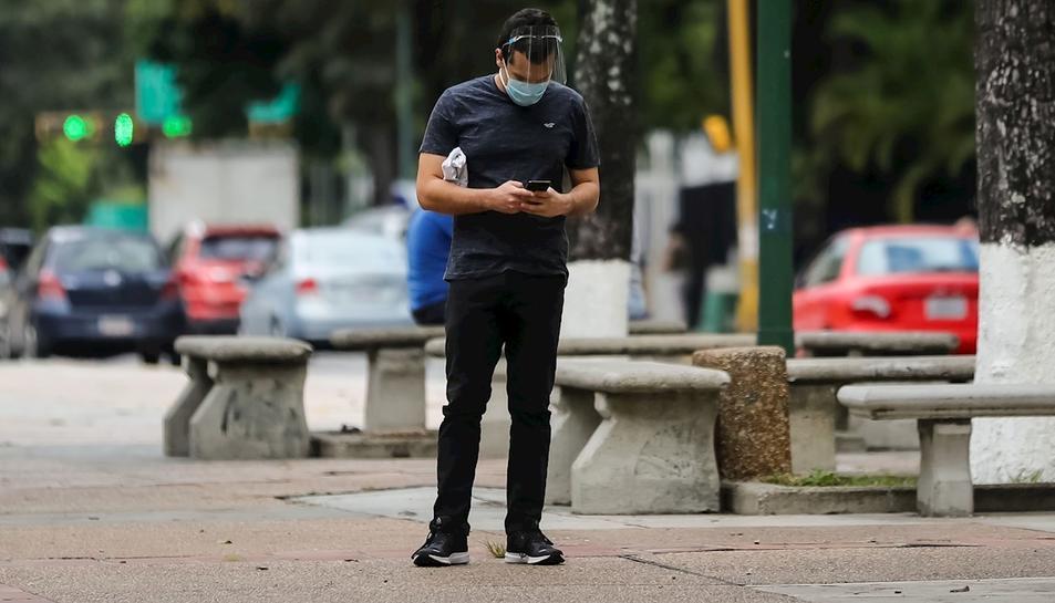 Un home consultant el mòbil al carrer.