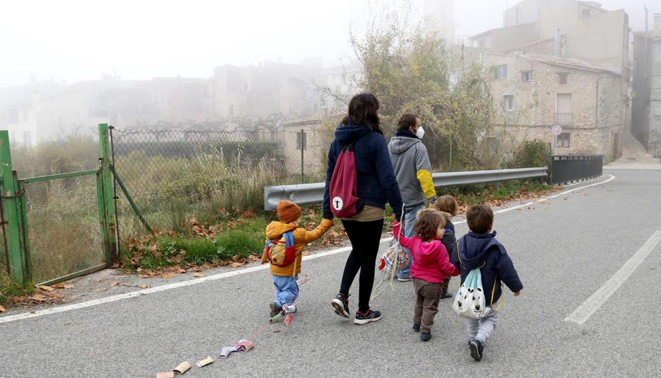 L'educadora i els infants de l'espai familiar d'autogestionat de La Muntanya d'Arbolí caminat pel poble d'esquenes.