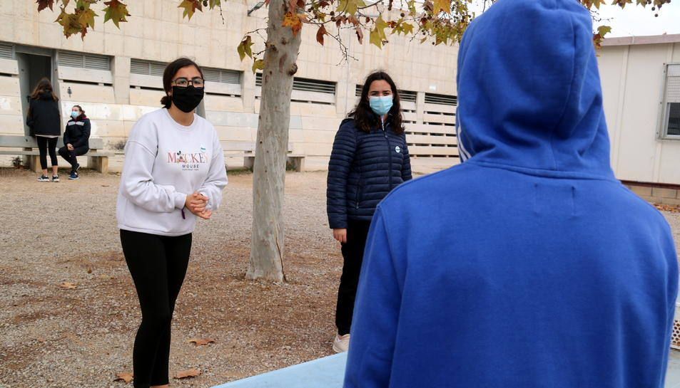 Un jove amb caputxa conversant sobre les mesures anticovid amb dues companyes de l'institut a Alcanar.