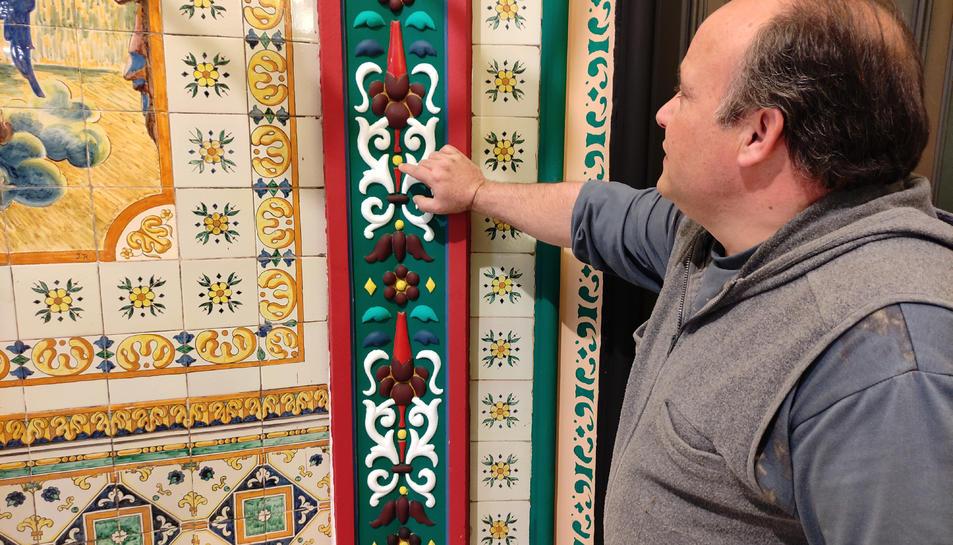 Josep Jiménez mostrant una de les pintures que ha restaurat.