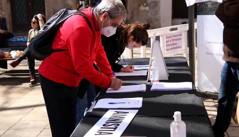 Dues persones signen a favor de la llei d'amnistia, en un acte d'Òmnium a Barcelona.