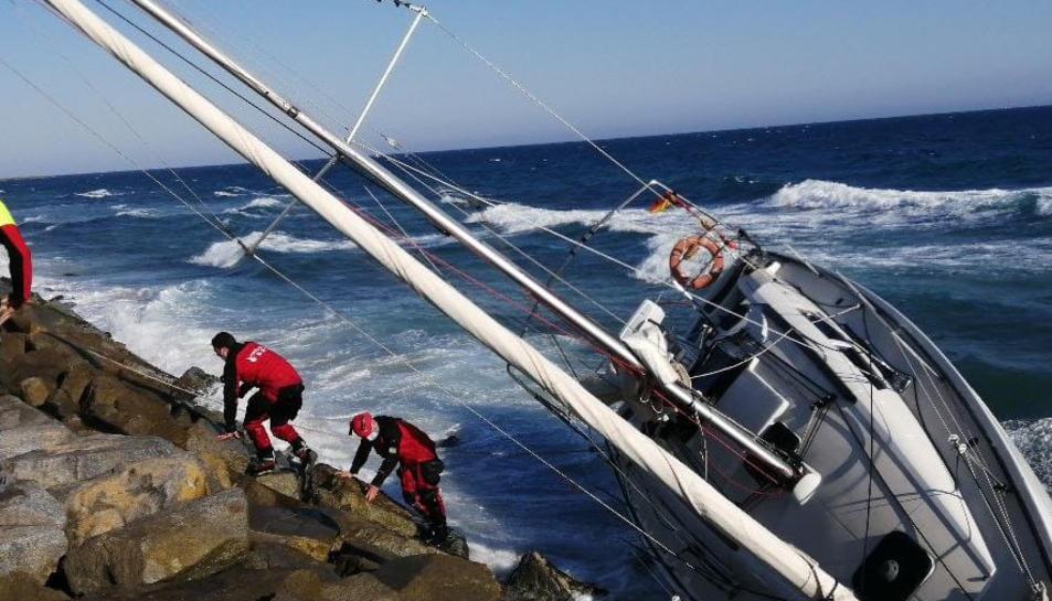 El veler atrapat a les roques amb els efectius dels Bombers treballant per evacuar les persones que estaven a dins.