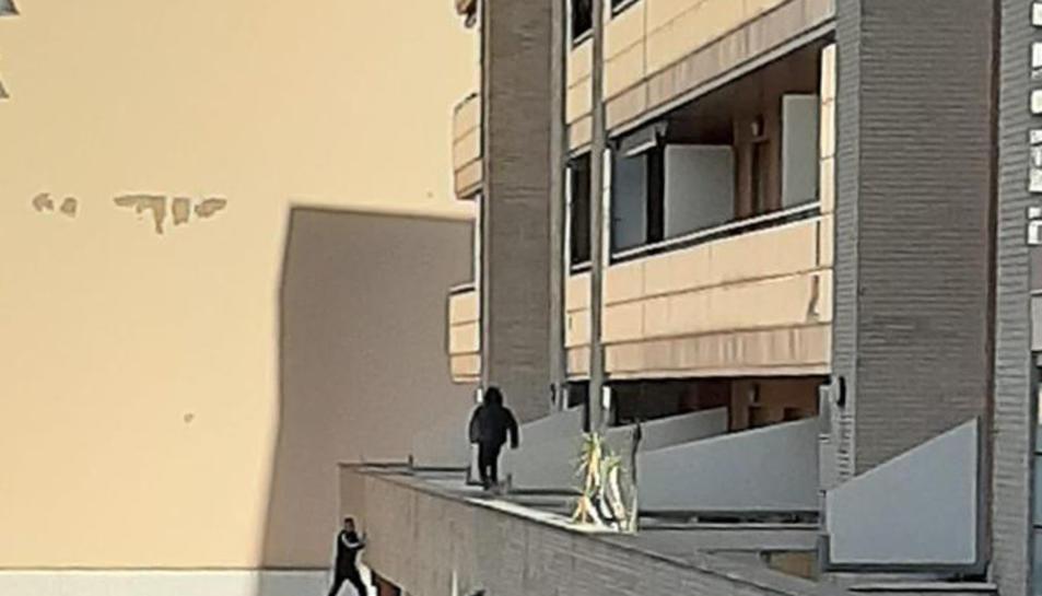 Uns nois s'enfilen per la façana d'un edifici per agafar una pilota.