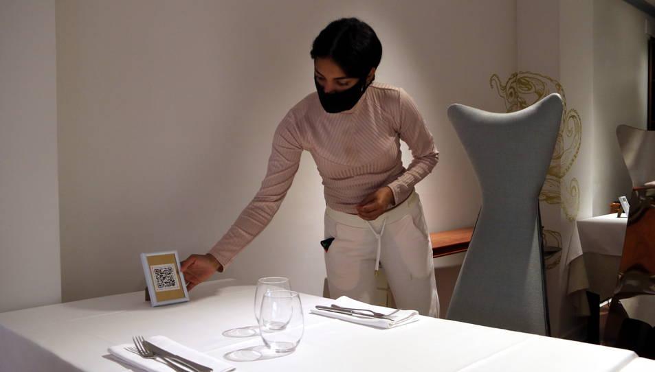 Una treballadora d'un dels restaurants de Cambrils preparant les taules abans de la reobertura dels negocis.