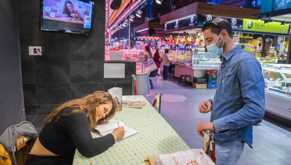 La cuinera de l'Ametlla de Mar signant el seu llibre.