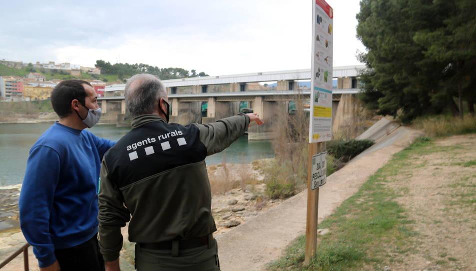 El cap dels Agents Rurals a l'Ebre, Miquel Àngel Garcia, i el biòleg del Grup Natura Freixe, Arnau Pou, assenyalant els marges de la presa de Flix.