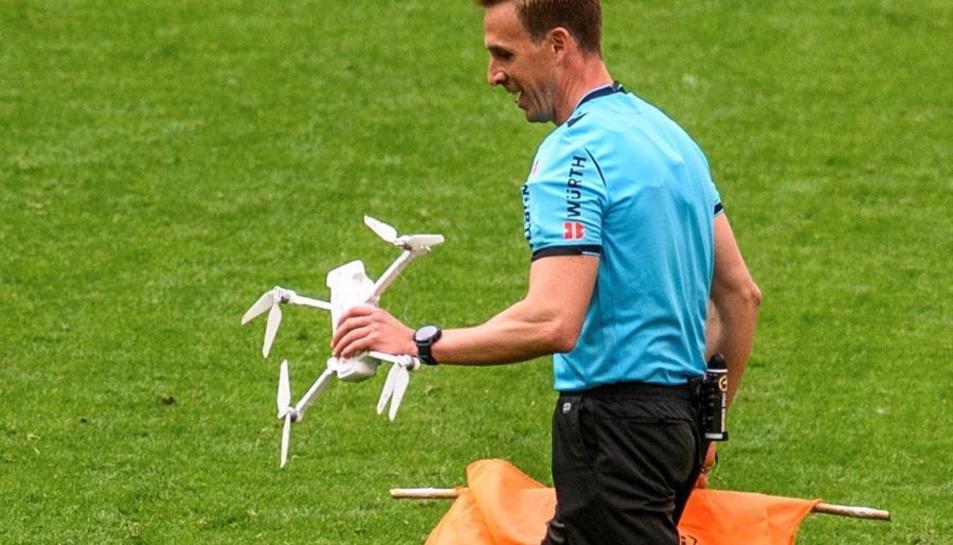 El col·legiat Valentín Pizarro retira un dron que ha caigut al terreny de joc durant el partit de LaLiga entre l'Athletic i l'Eibar celebrat aquest dissabte en San Mamés.