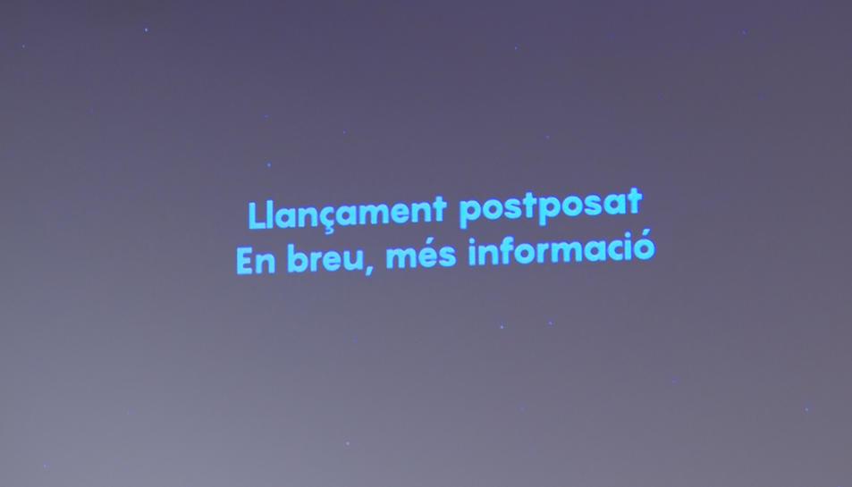 Una pantalla al CosmoCaixa informa que s'ha posposat el llançament de primer satèl·lit de la Generalitat