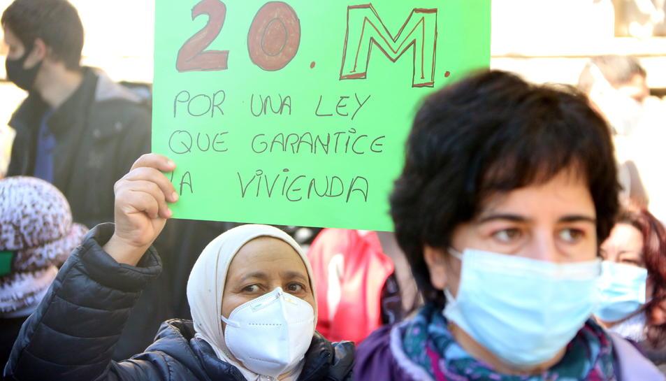 Una dona aixeca una pancarta a la manifestació del moviment per l'habitatge.