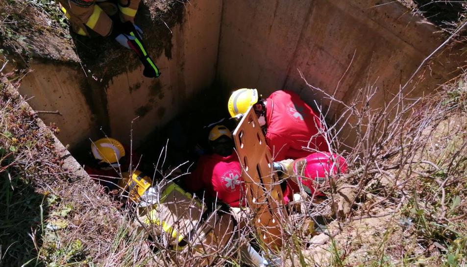 Els Bombers i el SEM treballant al pou de desguàs on han caigut els dos motoristes.