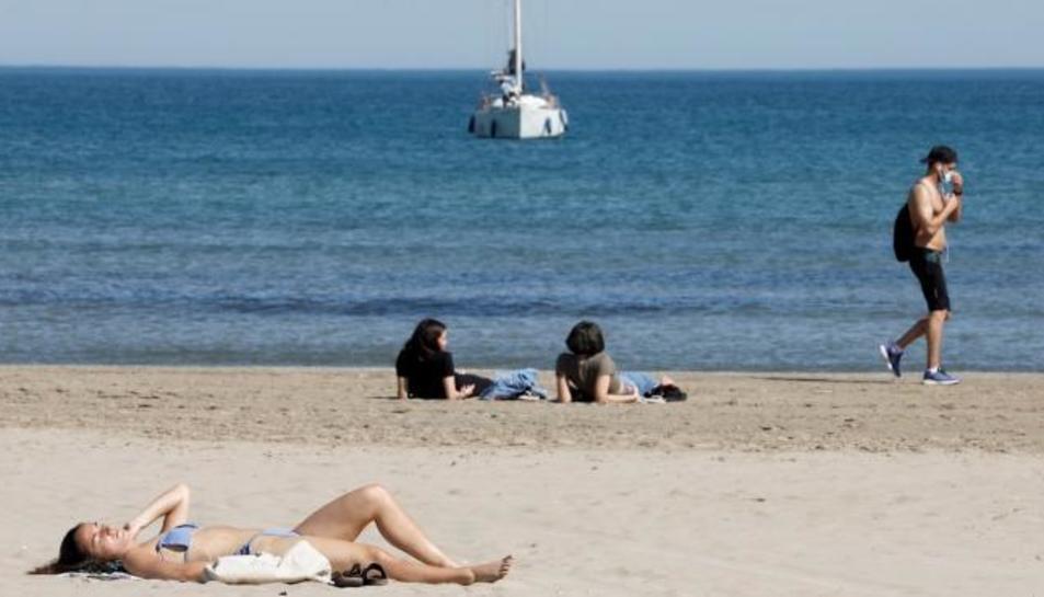 Varies persones prenent el sol a València.
