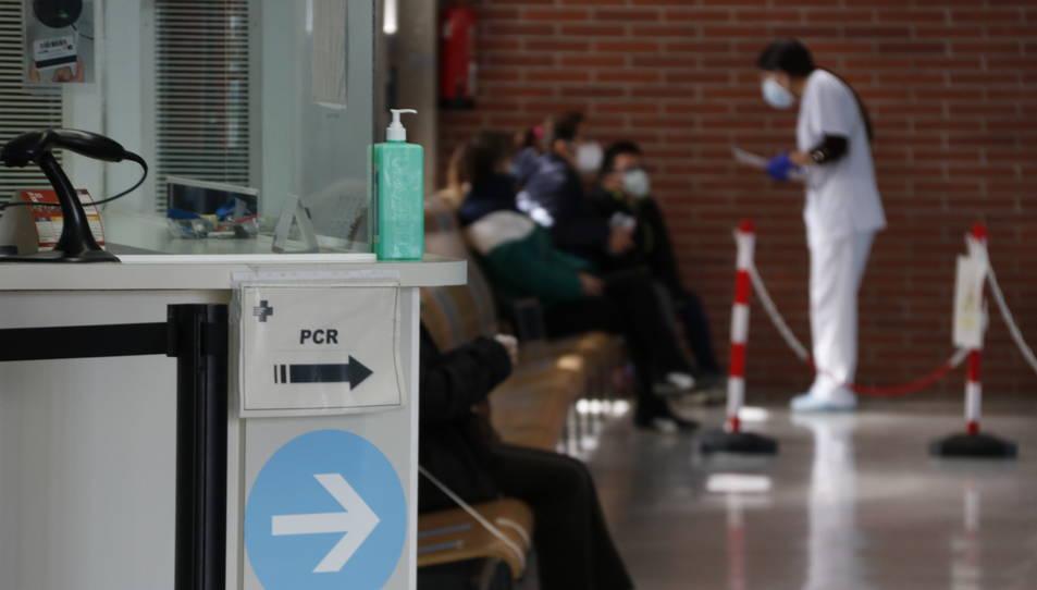 Una infermera atenent pacients al CAP de Montblanc, amb cartells indicant les proves PCR.