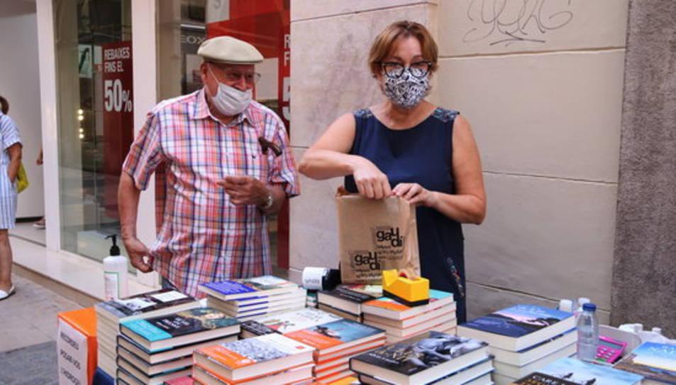 Un client comprant un llibre en la parada de la llibreria Gaudí de Reus en el Sant Jordi d'estiu.