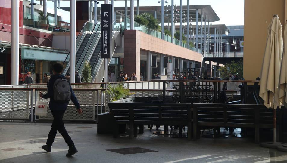 Un noi passejant pel costat de taules i cadires enretirades a un punt del centre comercial La Maquinista.