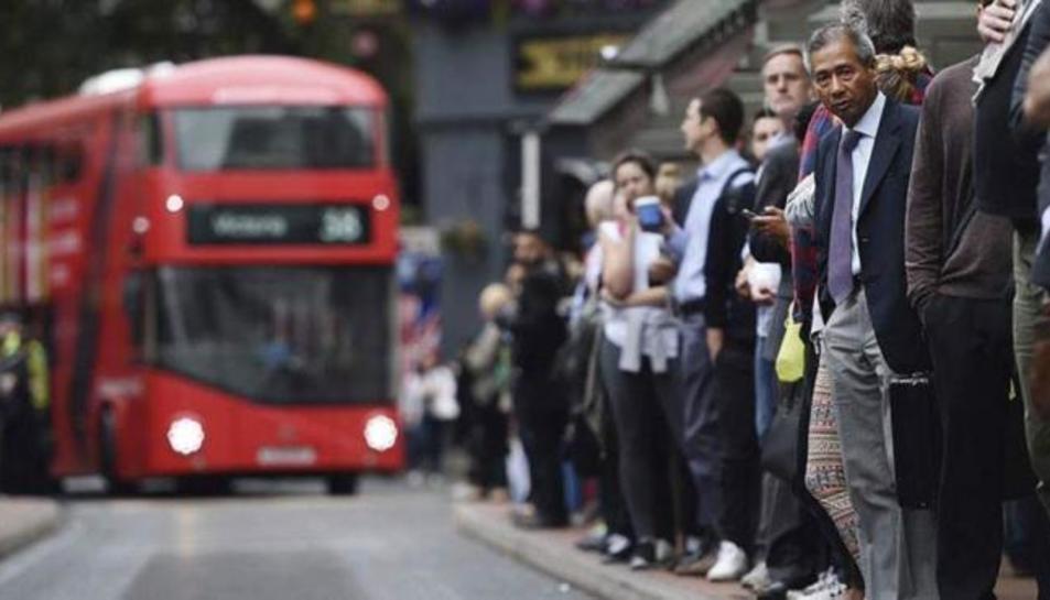 Treballadors esperen en una parada d'autobús de Londres.