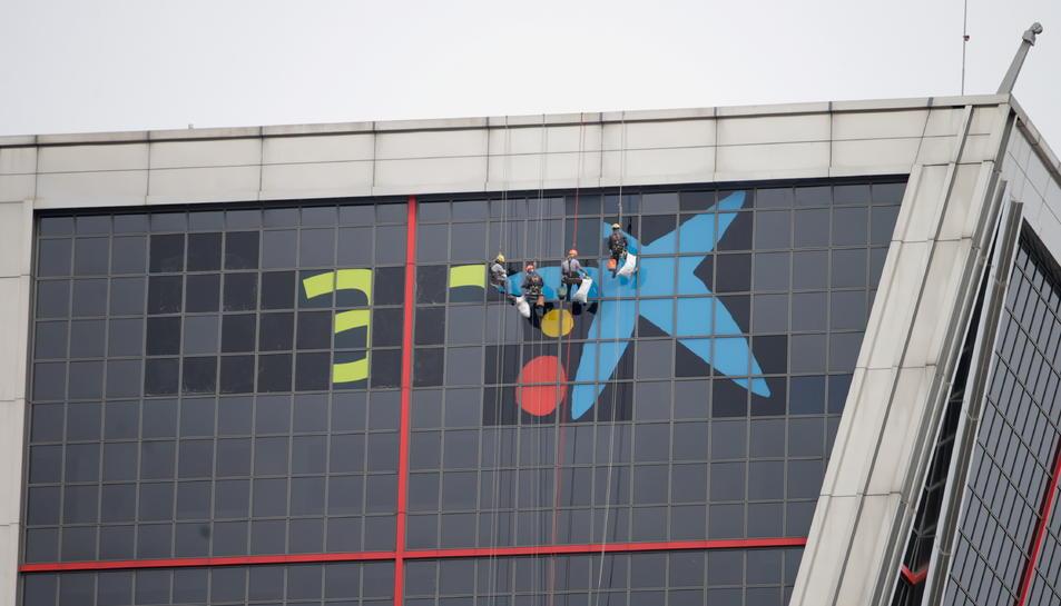 Operaris retiren el logo de Bankia de la seu de l'entitat a Madrid i hi col·loquen el de CaixaBank.