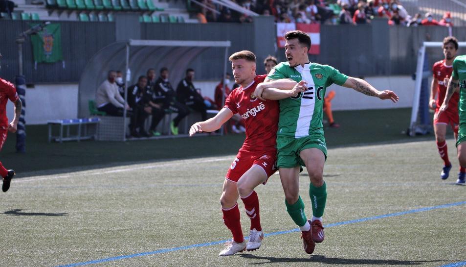 Pol Domingo lluitant amb un jugador del Cornellà durant el partit.